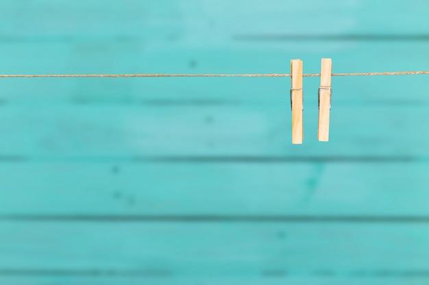 青い木製の背景上ロープ上の2つの洗濯はさみ