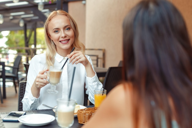 カフェのテーブルのそばに座っている2つの美しい若い女の子