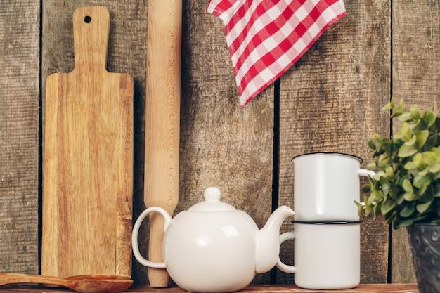 2つの白いビンテージティーマグカップとキッチンカウンターのティーポット