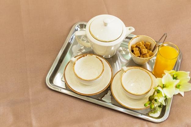 トレイ白いベッド、朝食の概念上の2つの白いマグカップ
