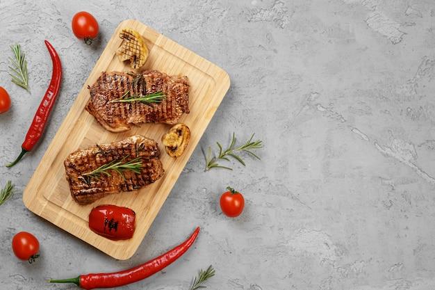 木の板、上面に2つのグリルしたビーフステーキ