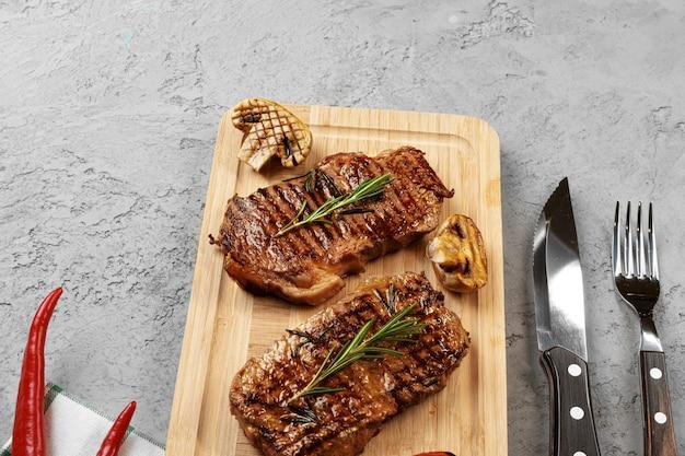 木の板に2つの牛肉のグリルステーキ