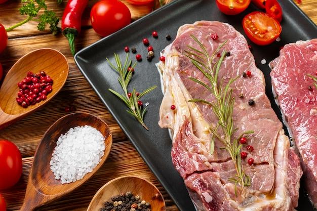 暗い木製のテーブルに2つの生の牛肉ステーキ