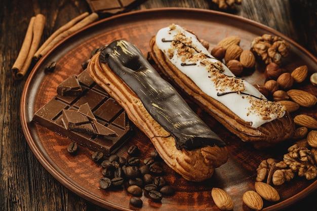 ナッツとコーヒーで飾られた2つの艶をかけられたエクレア