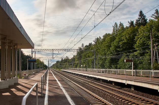 2つの方向にレールとプラットフォームがある郊外の鉄道駅