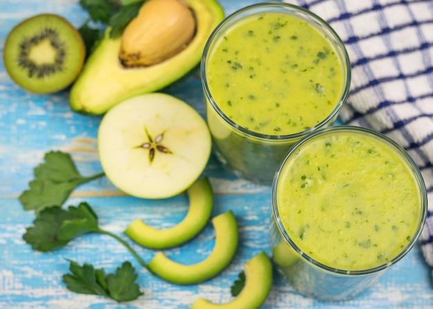 青いビンテージテーブルにアボカド、バナナ、キウイ、ハーブのスムージーと2つのガラスカップ。ダイエット菜食。