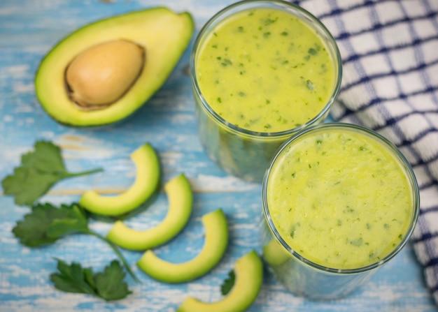 アボカド、バナナ、キウイ、青い木製のテーブルにハーブのスムージーと2つのガラスカップ。ダイエット菜食。
