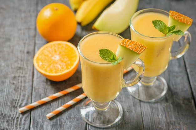 暗いテーブルにメロンスムージー、オレンジ、メロンが入った2つのガラスのマグカップ。