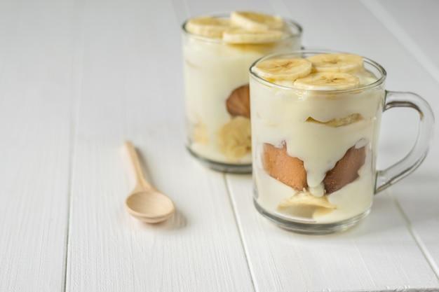 バナナプディングと白いテーブルの上の木のスプーンで2つのガラスカップ。ミルクとバナナのデザート。