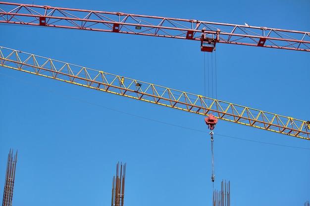 青い空、選択と集中に対して並列に配置された建設用クレーンの2つの矢印のクローズアップ