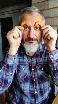 幸せな大人のひげを生やした男は眉の上に2か月の形のクッキーを保持し、眉、クッキーの楽しいコンセプトを描いています