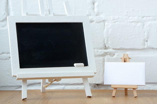 白いレンガの壁に2つのミニチュアチョークボードのクローズアップ