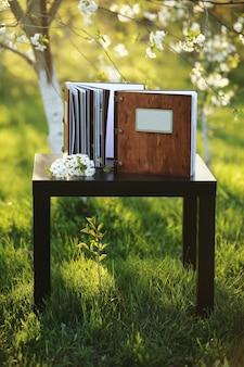自然の中のテーブルの上の2つの木製の写真集。碑文の場所