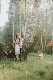 公園で娘と家族写真ママ。春の時間、楽しんで娘と美しい女性屋外で2人のかわいい子供を持つ若い母親の写真