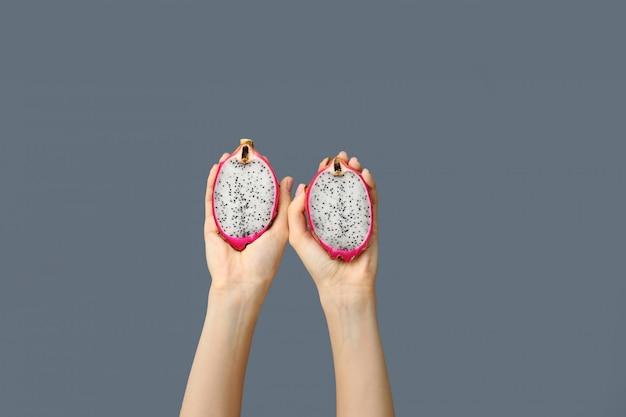 灰色の2つの半分のドラゴンフルーツまたはピタヤを保持している女性の手。活気に満ちた健康食品のアイデア。
