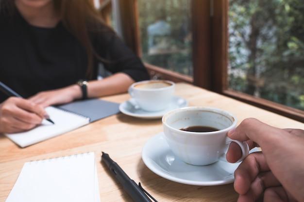 話しているとオフィスで会議しながらコーヒーを飲む2つのビジネスマンのクローズアップ画像