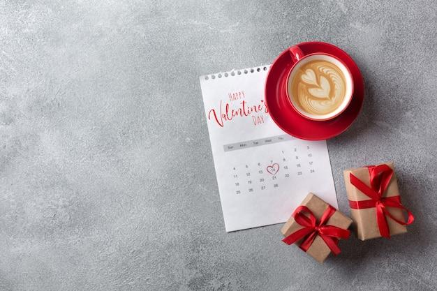 バレンタインの日グリーティングカード。 2月のカレンダーに赤いコーヒーカップとギフトボックス。