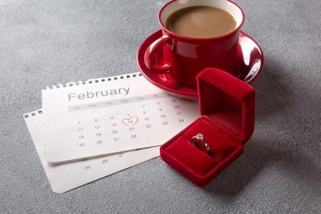 バレンタインのグリーティングカード。 2月のカレンダーに赤いコーヒーカップ、指輪、ギフトボックス。