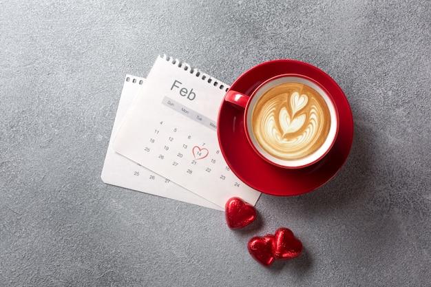 バレンタインのグリーティングカード。赤いコーヒーカップと2月のカレンダーにキャンディー。上からの眺め