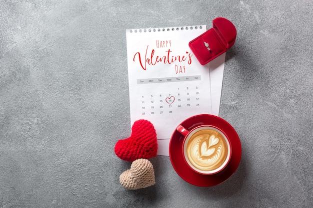 バレンタインのグリーティングカード。 2月のカレンダーに赤いコーヒーカップ、指輪、ギフトボックス。上からの眺め