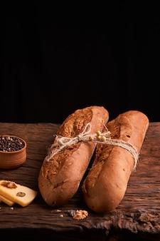 暗い木製のテーブルに2つの新鮮なバゲット。セレクティブフォーカス