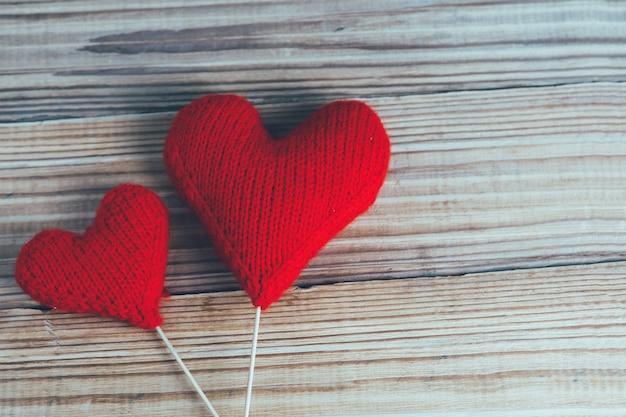 木製の背景に2つの赤いニットハート。バレンタインデーのコンセプト