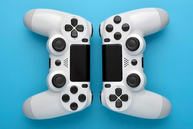 青の背景に2つのゲームコントローラー。ゲームのコンセプト競争の概念上面図。