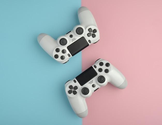 コンピュータゲームの競争ゲームのコンセプト色の背景上の2つの白いジョイスティック。