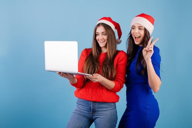 青で分離された幸せなジェスチャーでノートパソコンを見てサンタ帽子をかぶっている2人の笑顔の女性