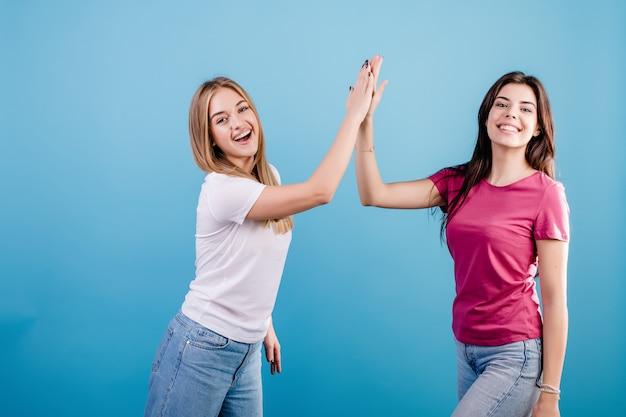 お互いにハイファイブを与える2人の若い美しい女性