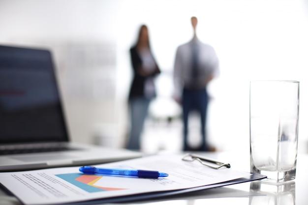 バックグラウンドで立っている2人のビジネス人々の机の上のフォルダーとラップトップコンピューター