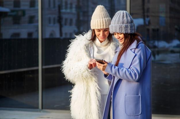 2人の面白い女性友人が笑って、屋外のスマートフォンでソーシャルメディアビデオを共有