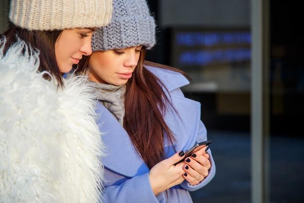 2人の若い女の子が一緒に屋外で電話を使っています