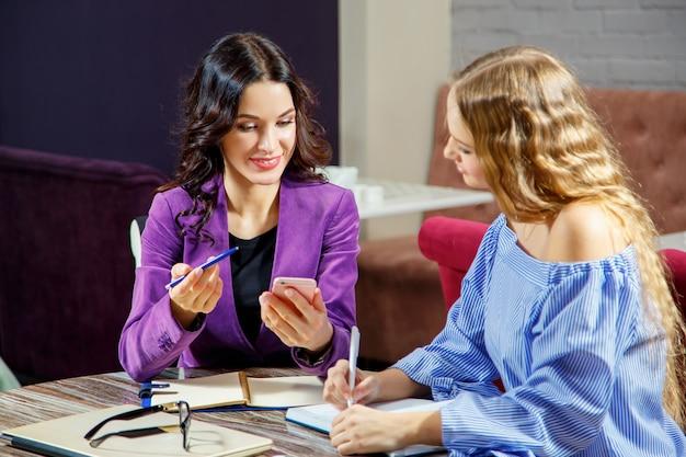 2人のフリーランサーが、カフェに座っている間に新しいプロジェクトについて議論しています