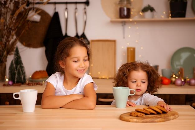 クリスマスキッチンで朝食を持っている2つの女の赤ちゃん
