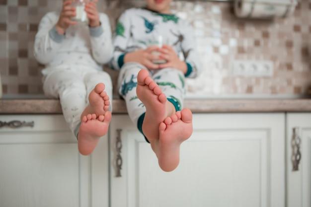 2人の赤ちゃん男の子はパジャマで台所で朝食を楽しんでいます