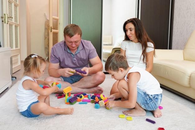 幸せな若い親と家で遊ぶ2人の小さな子供