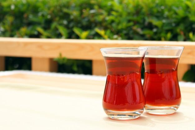 2 стекла турецкого чая в традиционной чашке на деревянном столе.