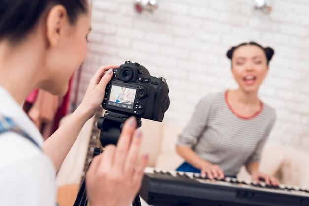 2人のファッションブロガーの女の子がキーボードを弾く