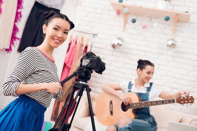 スカート付きシャツの2人のファッションブロガーの女の子がギターを弾く