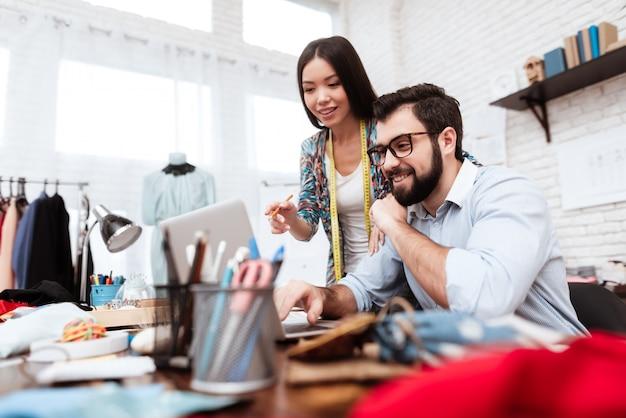 ノートパソコンを見ている2人のファッション・デザイナー。