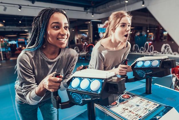2人の美しい女の子がビデオゲームでスターシップを率いています。