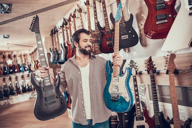大人のひげを生やした男は、2つのエレクトリックギターの間で選択を行います。