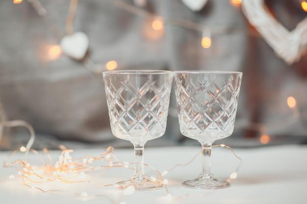 聖バレンタインの日カード。明るいボケ味を持つ2つの空のワイングラス。背景にガーランドライトと白い木製の心。