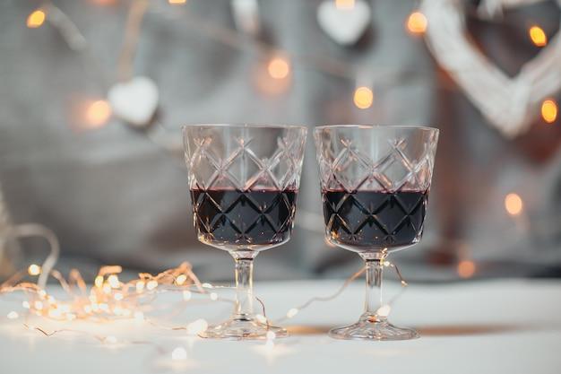 聖バレンタインの日カード。明るいボケ味を持つ2つのワイングラス。背景にガーランドライトと白い木製の心。グラスの赤ワイン。