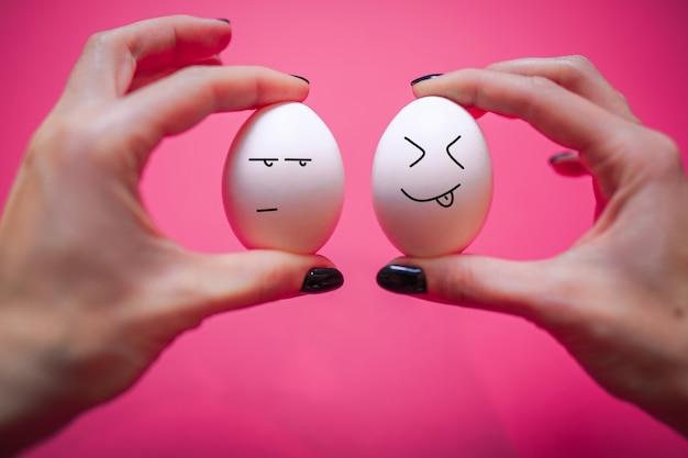 顔と感情の卵。コピースペースでハッピーイースターカード。白い卵。女性は2つの白い卵を手で保持しています。