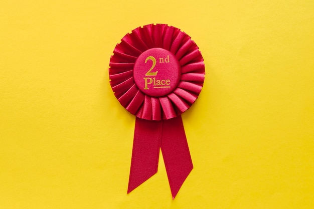 2nd place red winners ribbon rosette on yellow