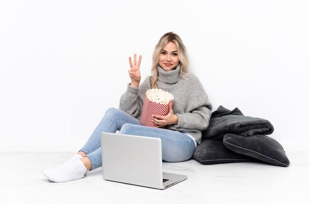 幸せとラップトップで3つの指で映画を見ながらポップコーンを食べて10代のブロンドの女の子