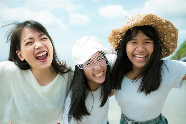 3つのアジアの若い女性と海のビーチで幸せな10代