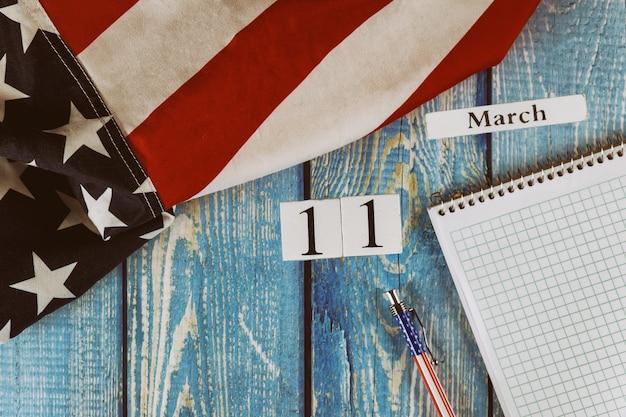 3月11日カレンダー日空のメモ帳とオフィスの木製テーブルの上のペンで自由と民主主義のアメリカ合衆国のシンボルの旗